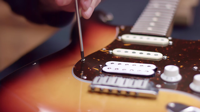 Man repairing a guitar, tightens the screw