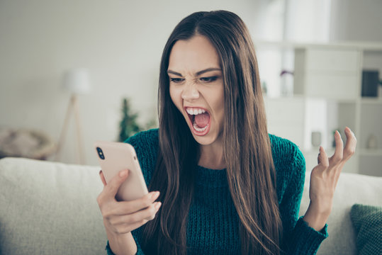 Closeup photo portrait of angry aggressive crazy unsatisfied holding looking at screen monitor she her lady wearing green casual pullover sweater