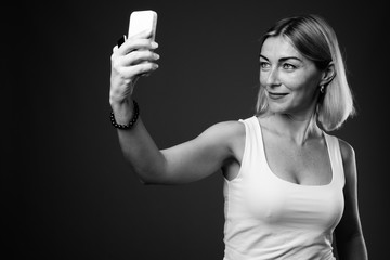 Beautiful businesswoman with short hair taking selfie with phone
