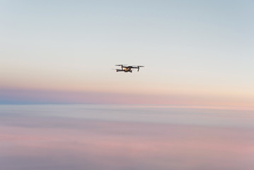 Drone quadcopter with digital camera above sunset sky and Earth Surface. Concept of global monitoring and control
