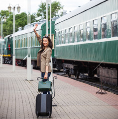 smiling beautiful middle-aged woman with a suitcase and handbag