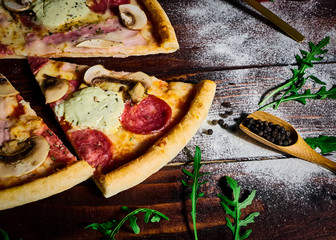 Italian fast food. Delicious hot pizza sliced and served on wooden platter with ingredients, close up view. Menu photo.