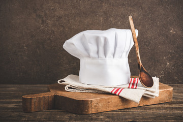 Chef's hat, antique cutting board and wooden spoon