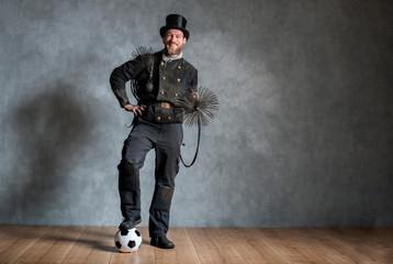 Fußball spielender Schornsteinfeger in Arbeitskleidung und mit Kehrgeräten steht vor Betonwand