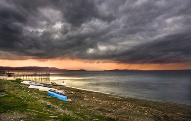 Dramatic sunset landscape at Urla, Izmir, Turkey. Beautiful blazing sunset landscape over bright blue sea and orange cloudy sky above it with awesome golden rays of sun light reflection on calm waves.