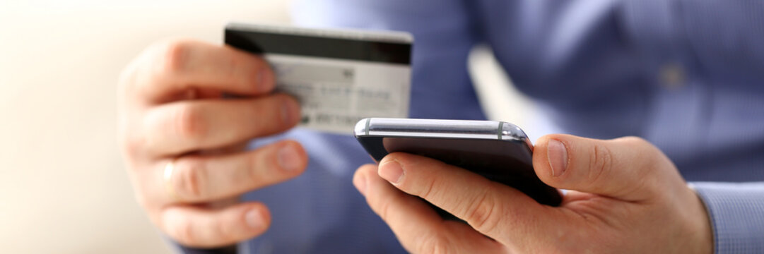 Male arms in suit hold credit card and phone make transfer