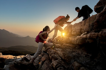 Group of Asia hiking help each other silhouette in mountains with sunlight.. Wall mural