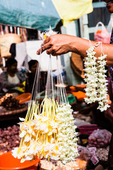 A vendor carries strands of flower garlands to sell at a local market.