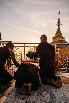 Monks in maroon robes kneel at sunset to light candles and incense in front of giant gold-leaf gilded rock and stupa.
