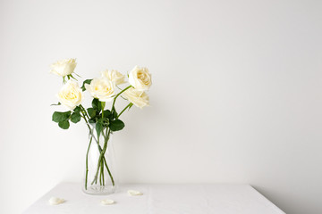 White roses in a glass vase on white table top on white background with copy space for product mockup placement for valentine's day wedding ceremony