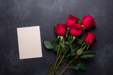 Red rose flowers bouquet on black stone background Valentine's day greeting card Top view Copy space