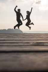 Young couple holding hands jumping in the air