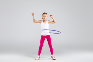 Smiling girl doing exercises with hula hoop