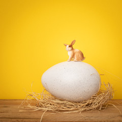 sweet Easter Bunny is sitting on a big egg yellow background