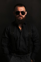 young handsome man with big beard and black sunglasses on black background  close up portrait