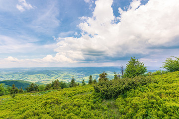 view in to the valley from grassy hill. beautiful summer scenery in mountains. dynamic cloudscape on a blue sky.