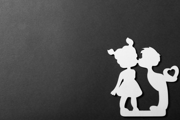 figures of kissing boy and girl with gift heart on black background, first love concept