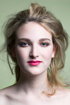 Beautiful, young woman wearing red lipstick and her blond hair in a loose updo, portrait.