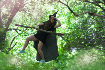witch flying on a broom. an attractive girl