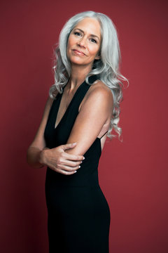 Portrait of a beautiful woman with long, silvery, grey hair wearing a black evening dress.
