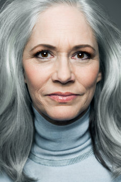 Mature woman with long, silvery, grey hair wearing a light blue turtleneck sweater, portrait.