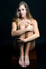 Naked, young woman sitting down and hugging her knees in front of a black background, full length.
