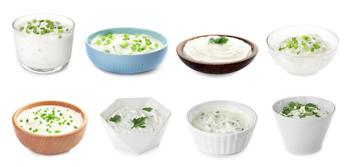 Set of delicious sour cream with herbs in bowls on white background