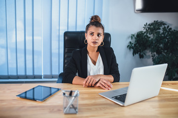 Young beautiful business lady dressed in a business stylish black jacket.