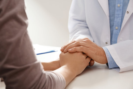 Male doctor comforting woman at table, closeup of hands. Help and support concept