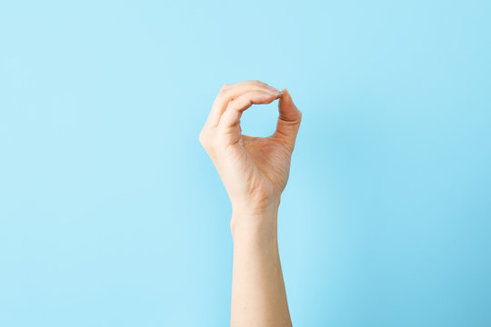 Woman showing O letter on color background, closeup. Sign language