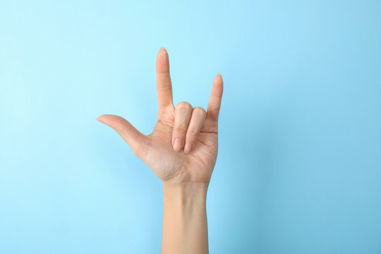 Woman showing hand sign on color background, closeup. Body language