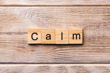 calm word written on wood block. calm text on wooden table for your desing, concept