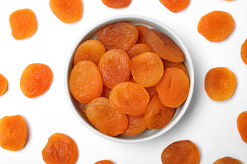 Flat lay composition with bowl of dried apricots on white background. Healthy fruit