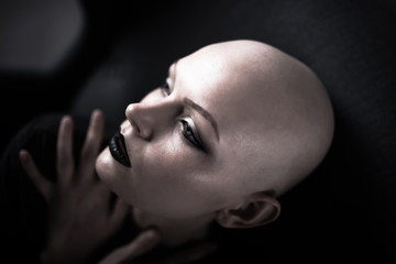 Emotive portrait of a beautiful bald woman while sitting on a chair.