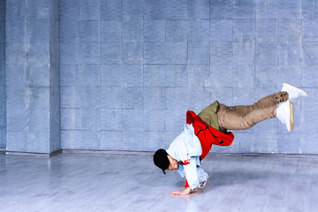 Young man standing on hands in dance. Fashion style dancer raised his leg standing on hands on grey floor. Rap dancer in movement.
