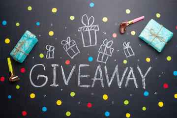 The inscription Giveaway is written on a blackboard with gifts. Free distribution, bloggers and gifts