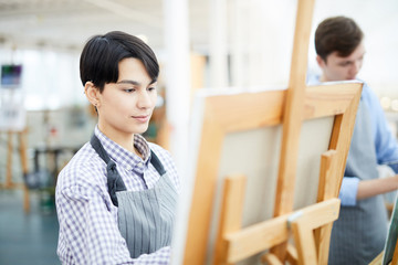 Portrait of female art student painting picture on easel enjoying work in studio, copy space