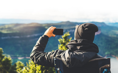 hipster tourist hold in hands smartphone taking photography click on mobile camera, photographer looking on gadget technology, panoramic landscape vacation concept, sun flare mountain