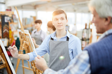 Waist up portrait of student in art class looking at teacher while painting picture on easel, copy space