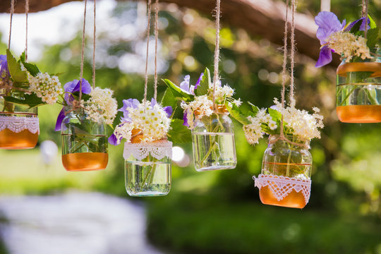 The beautiful flowers in the glasses holding on the cords outdoor