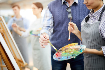 Mid section portrait of two unrecognizable artists holding palette mixing oil colors while painting picture on easel in art studio, copy space