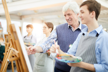 Waist up portrait of smiling art teacher helping student painting picture on easel during class, copy space