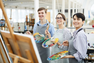 Waist up portrait of three cheerful art students looking at camera posing with easels and palettes in studio