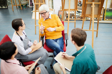 High angle portrait of mature art teacher talking to group of students sitting in circle in art studio