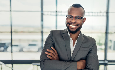Portrait of a confident black businessman smiling holding with his arms crossed