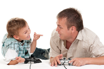 Dad and Son holding Joysticks and Playing Video Games on console together. Happy Family - Father and little Boy having Fun gaming on white background. Man with Child playing Computer Game.