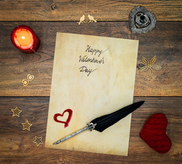 Vintage Valentine's card with red lit candle, red cuddle heart, wooden decorations, detailed silver quill stand accented by beautifully ornamented silver and black quill on antique oak - top view