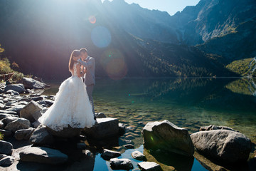 Romantic groom and bride in beautiful white wedding dress standing on the stony shore of the Morskie Oko lake in Poland. Scenic mountain view