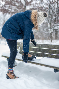 woman putting non slip snow cleats on boots for winter hike