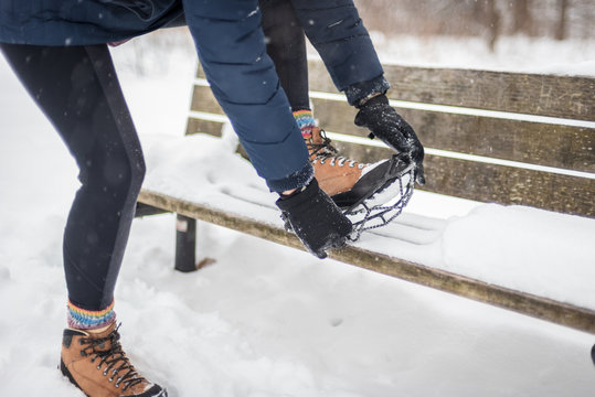 woman putting non slip snow cleat on hiking boot in winter
